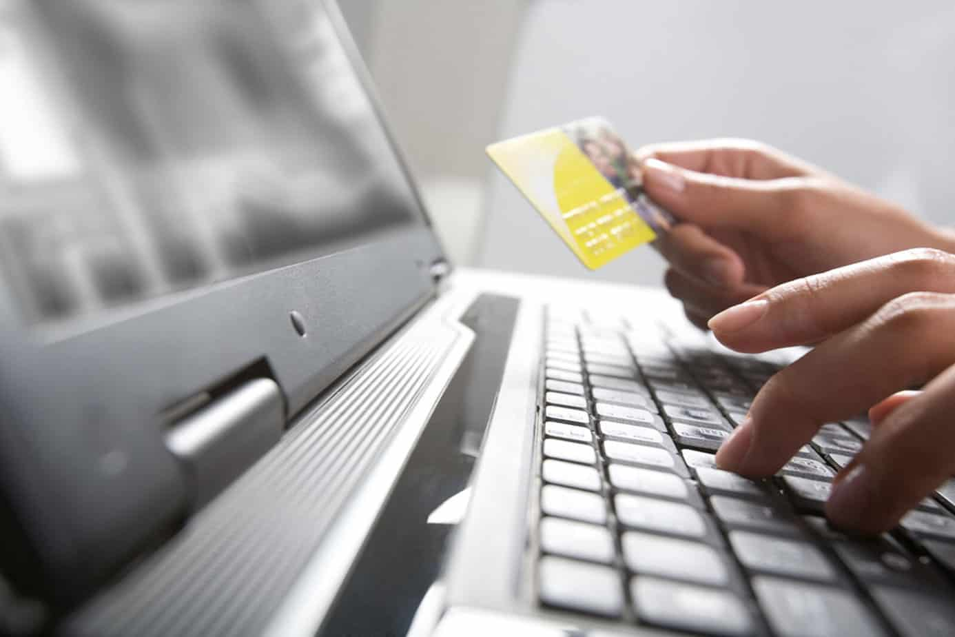 image of person processing credit card with ecommerce software for distributors